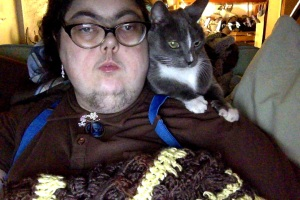 Me with Fey sitting on my shoulder, and a brown and yellow afghan in front of me.