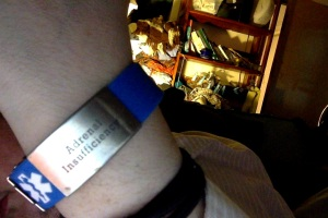 "Blue medical bracelet with a medical symbol in white and the words ""Adrenal Insufficency"" on a metal plate."