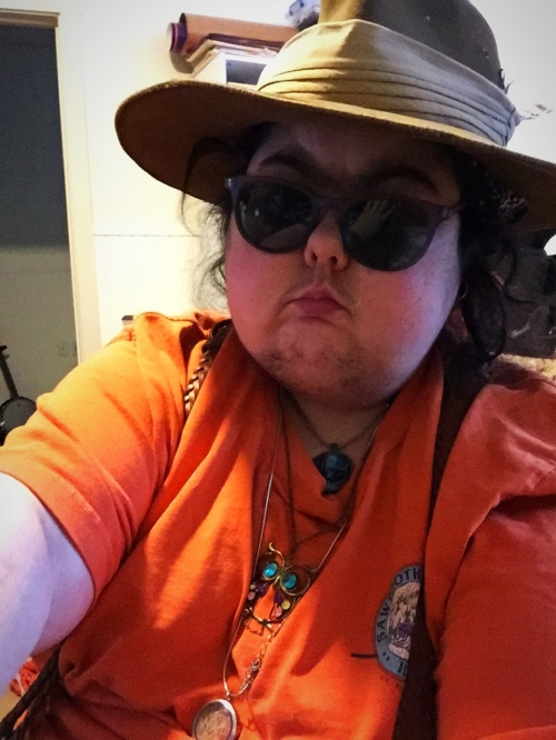 Mel wearing an orange shirt, dark glasses, and a brown Aussie hat.